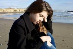 哀伤的少年想法的坐海滩在冬天 库存照片