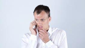 哀伤的年轻人谈话在手机 免版税库存照片