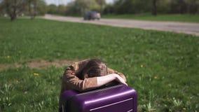 哀伤的旅客错过了她的飞行和公共汽车-坐她的行李手提箱和哭泣-一个白白种人的情感 股票录像