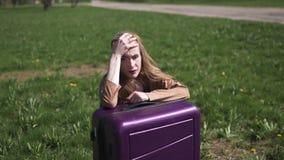 哀伤的旅客错过了她的飞行和公共汽车-坐她的行李手提箱和哭泣-一个白白种人的情感 股票视频