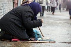哀伤的无家可归的妇女坐通过街道的人民  免版税库存照片