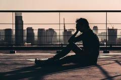 哀伤的沮丧的亚裔人丧失的希望和啼声剪影,坐大厦屋顶在日落,黑暗的心情口气 库存图片