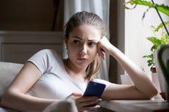 哀伤的沮丧的女性举行的智能手机坐长沙发 图库摄影