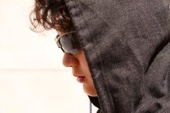 哀伤的混乱的拉美裔13岁佩带有冠乌鸦和黑暗太阳镜摆在的少年室外-接近  免版税图库摄影