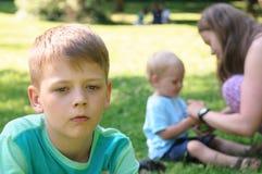 哀伤的男孩在庭院里 免版税库存图片