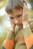 哀伤的男孩在秋天公园 免版税库存图片