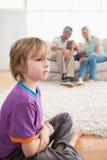 哀伤的男孩坐地板,当享用与姐妹时的父母 库存图片