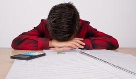 哀伤的男孩用在他的头的手在桌上在学校 免版税图库摄影