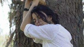 哀伤的疲乏的妇女在树关闭的眼睛附近站立,感觉室外自然的能量 股票视频