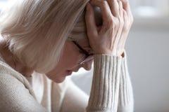 哀伤的疲乏的资深妇女对负顶头在感觉头疼的手上 库存图片