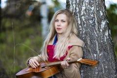 哀伤的秋天是白肤金发的与吉他坐地面由桦树 免版税库存照片