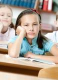 哀伤的美丽的女小学生在学校 免版税库存图片
