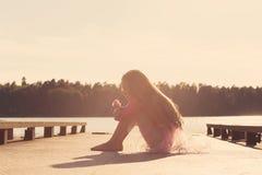 哀伤的美丽的青少年的女孩坐与严肃的面孔在海边 免版税库存图片