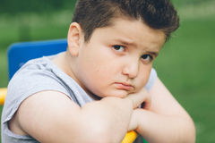 哀伤的肥胖男孩坐体育模拟器 免版税库存图片
