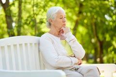 哀伤的资深妇女坐长凳在夏天公园 免版税库存照片