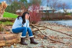 哀伤的青少年女孩坐沿多岩石的海滩的日志由湖 免版税库存图片