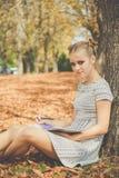 哀伤的青少年的女孩在有笔记本的秋天公园 库存照片