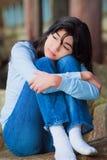哀伤的青少年的女孩坐沿湖岸,偏僻的表示的岩石 库存照片