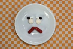 哀伤的面孔由医学制成 止痛药片剂 在瓷盘的色的药片 被分类的配药药片 免版税库存图片