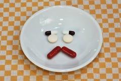 哀伤的面孔由医学制成 止痛药片剂 在瓷盘的色的药片 被分类的配药药片 免版税图库摄影
