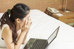 哀伤的年轻亚裔妇女与膝上型计算机一起使用在卧室 库存照片