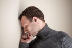 哀伤的年轻人休息了他的头和拳头在墙壁上 免版税库存照片