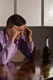 哀伤的年轻人喝威士忌酒 库存图片