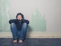 哀伤的年轻人在空的屋子里 免版税库存图片