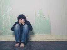 哀伤的年轻人在空的屋子里 库存图片