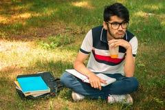 哀伤的年轻学生在手和书上坐一棵草用在旁边咖啡 库存图片
