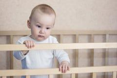 哀伤的婴孩是在轻便小床 库存图片