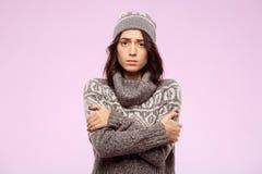 哀伤的年轻美丽的在轻的背景的女孩感觉的寒冷 免版税库存照片