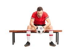 哀伤的年轻足球运动员坐长凳 免版税库存照片