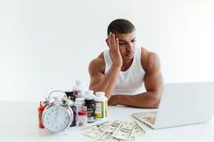 哀伤的年轻运动员近似货币和使用膝上型计算机的体育营养 免版税图库摄影