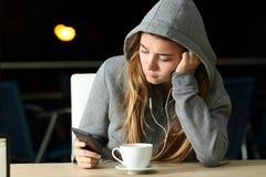 哀伤青少年听到与一个巧妙的电话和耳机的音乐 库存照片