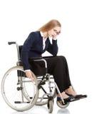 哀伤,严肃的女商人坐轮椅。 免版税库存照片