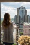 哀伤年轻美丽的白肤金发的女孩站立与她在窗口里和 图库摄影