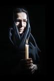 哀痛的哀伤的老妇人前辈与蜡烛 免版税库存照片