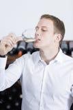 品尝一杯白葡萄酒的人 免版税库存照片