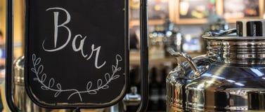 品尝与发光的不锈钢罐的酒吧标志 图库摄影