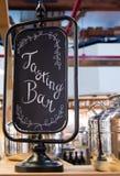 品尝与发光的不锈钢罐的酒吧标志 库存图片