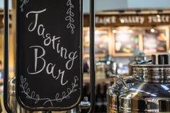 品尝与发光的不锈钢罐的酒吧标志 免版税图库摄影