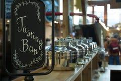 品尝与美丽的银色平底锅和罐的酒吧标志在背景 免版税库存图片