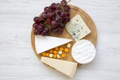 品尝乳酪的各种各样的类型用在一个圆的木板的葡萄 酒的,顶视图食物 平的位置 免版税图库摄影