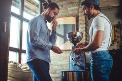 品尝从烘烤器的男性所有者咖啡豆 免版税图库摄影