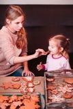 品尝圣诞节姜饼曲奇饼的姐妹 库存照片