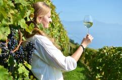 品尝在葡萄园中的女孩白葡萄酒 免版税图库摄影