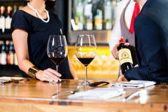 品尝在酒吧的亚洲夫妇红葡萄酒 免版税库存图片