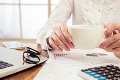 品尝她的早晨咖啡的女实业家 免版税图库摄影