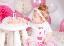 品尝她的生日蛋糕的婴孩 免版税库存图片